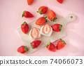 一護大福的橫斷面在木板上。環繞著它的草莓的鳥瞰圖。白豆沙粉紅色背景 74066073