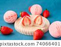 在木板上的草莓在大福的橫斷面附近的草莓。在藍色背景的桃紅色紙pom。白豆沙 74066401