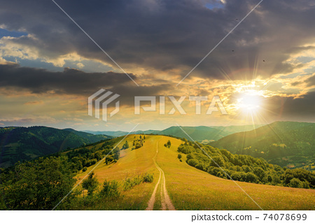 road through meadow in mountains at sunset. beautiful rural landscape of carpathians in evening light. wonderful summer weather with fluffy clouds on the sky 74078699