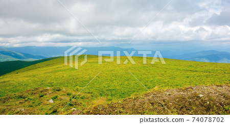 mountain landscape in summer on a cloudy day. grass covered hillside meadow. carpathian watershed ridge in the distance 74078702