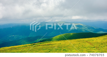 mountain landscape in summer on a cloudy day. grass covered hillside meadow. carpathian watershed ridge in the distance 74078703