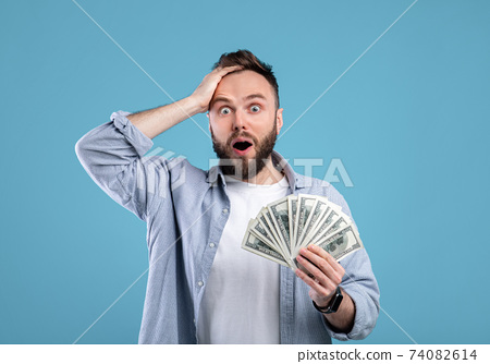 Shocked young guy holding lots of money, cannot believe his big win or luck over blue studio background 74082614