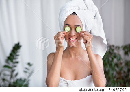 Cheerful young african american lady in towel with clean pure skin taking relaxing 74082795