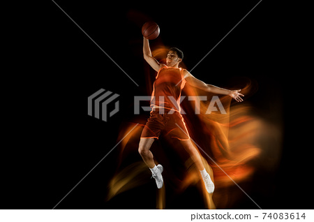 Young arabian basketball player of team in action, motion isolated on black background in mixed light. Concept of sport, movement, energy and dynamic. 74083614