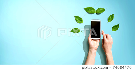 Person holding smartphone with green leaves 74084476