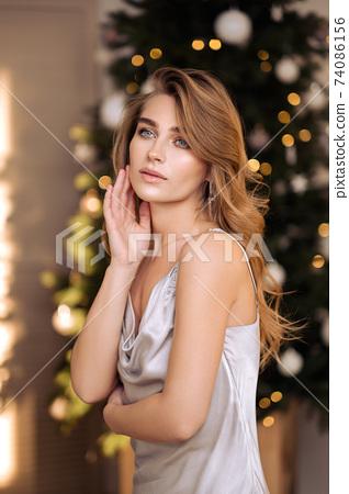 Sensual beauty portrait close-up of a beautiful blonde woman. Long hair, blue eyes, gray shiny dress. 74086156