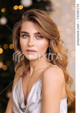Sensual beauty portrait close-up of a beautiful blonde woman. Long hair, blue eyes, gray shiny dress. 74086158