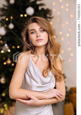 Sensual beauty portrait close-up of a beautiful blonde woman. Long hair, blue eyes, gray shiny dress. 74086163