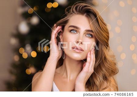 Sensual beauty portrait close-up of a beautiful blonde woman. Long hair, blue eyes, gray shiny dress. 74086165