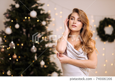 Portrait of a young pretty and dreamy blonde woman with a silver dress against the backdrop of the Christmas tree. 74086166