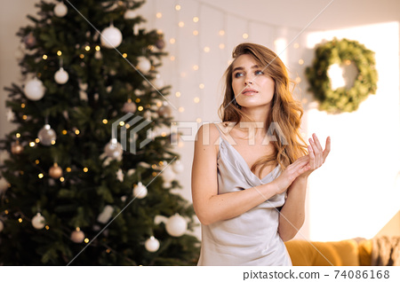 Portrait of a young pretty and dreamy blonde woman with a silver dress against the backdrop of the Christmas tree. 74086168
