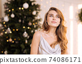 Portrait of a young pretty and dreamy blonde woman with a silver dress against the backdrop of the Christmas tree. 74086171