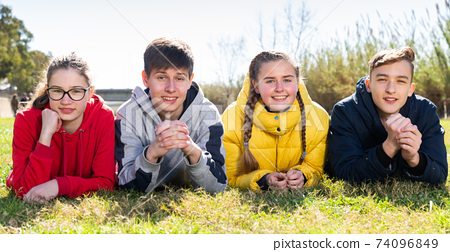 Portrait of teenagers lying on grass in park 74096849