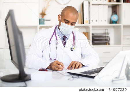 Latin American doctor wearing face mask while writing notes and reading something on laptop at his office 74097229