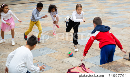 Group of happy schoolchildren playing football together 74097764