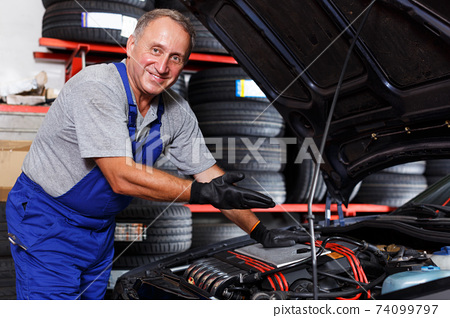 mechanic showing car after repair 74099797