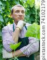 Farmer controlling growth of zucchini 74102179
