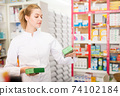 Young friendly female pharmacist suggesting useful tablets in pharmacy 74102184