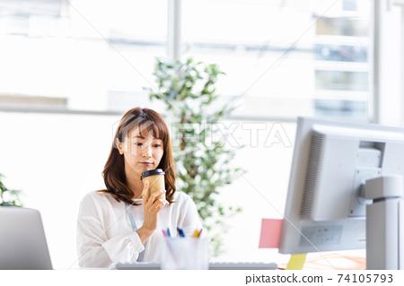 女人在桌子上工作與外賣杯 74105793