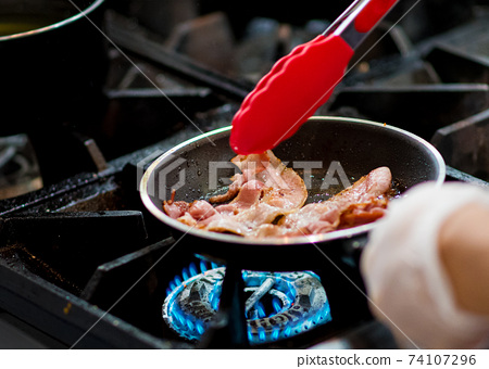 fresh fried bacon in a pan, Chef cooking in the kitchen 74107296