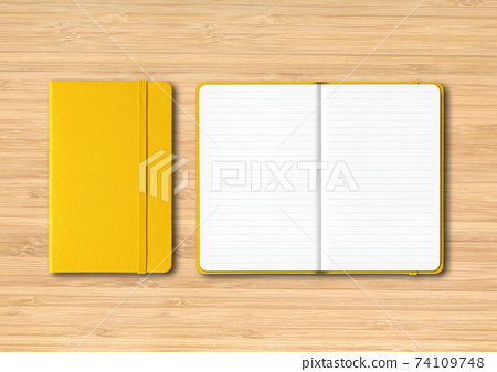 Yellow closed and open lined notebooks on wooden background 74109748