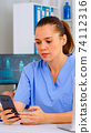Medical nurse consulting patient online using smartphone 74112316