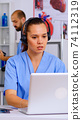 Medical assistant operator with headphone consulting patients 74112319