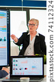 Elderly project manager pointing at desktop presenting statistical data, 74112324