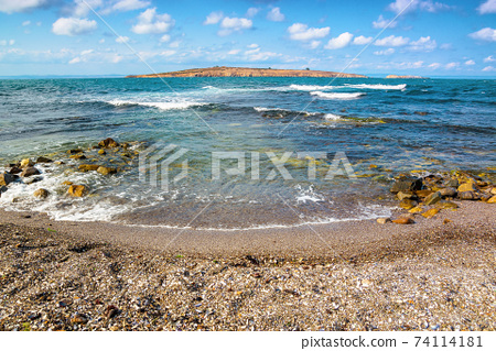 seascape with island in the distance. beautiful landscape of bulgaria near sozopol. waves crashing rocky shore. sunny weather with fluffy clouds on the sky 74114181