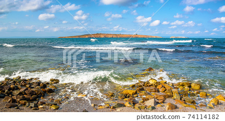 seascape with island in the distance. beautiful landscape of bulgaria near sozopol. waves crashing rocky shore. sunny weather with fluffy clouds on the sky 74114182