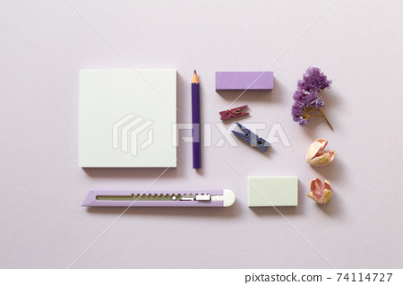 Notepad, cutter, colored pencil, clip, eraser on purple background. flat lay, top view, copy space. Work and study place 74114727