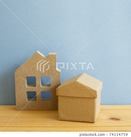 House model on wooden table. Blue background, copy space. Real estate concept 74114759