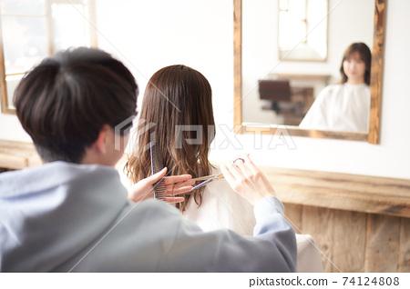 剪女人的頭髮的美髮師 74124808