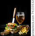Burger with a knife,fries, beer in a glass. 74133532