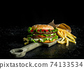 Burger with fries on the cutting Board. 74133534