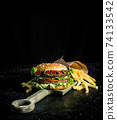 Burger with fries on the cutting Board. 74133542