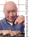 老人在烤雞肉串上撒鹽 74149521