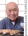 老人在吃烤雞肉串時喝清酒 74149522