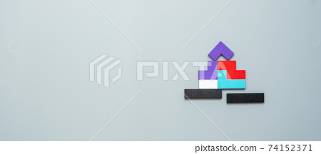 Home shape block with colorful wood puzzle pieces on gray background. logical thinking, business logic, solutions, rational, house, real estate and strategy concepts 74152371