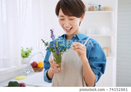 有花的一個微笑的中間婦女在廚房裡 74152861