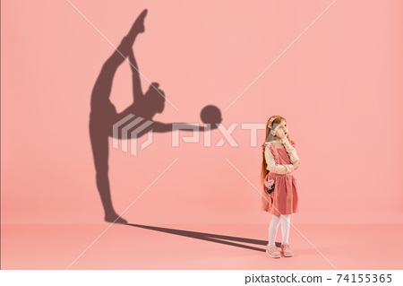 Childhood and dream about big and famous future. Conceptual image with girl and shadow of fit female rhythmic gymnast on coral pink background 74155365