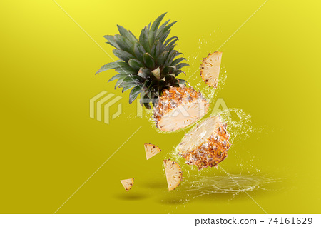 Water Splashing on Split Pineapple Fruit isolated over yellow background 74161629