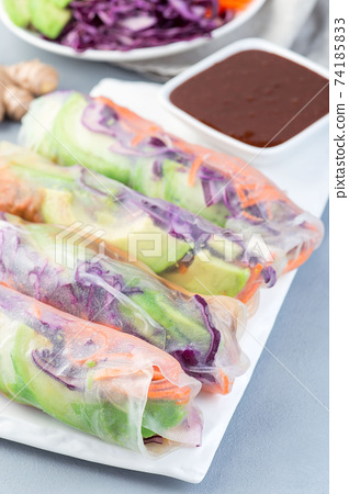 Vegetarian spring rolls with tofu and vegetables, served with soy and peanut butter sauce, on white plate, vertical 74185833