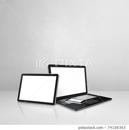Laptop, mobile phone and digital tablet pc on white concrete office desk 74186363