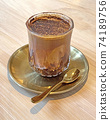 Glass of dirty mocha drink with golden tea spoon and dish on wooden table 74189756
