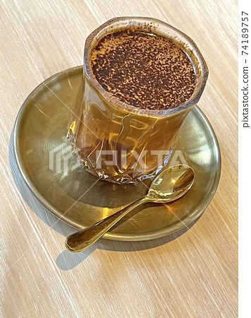 Glass of dirty mocha drink with golden tea spoon and dish on wooden table 74189757