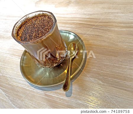 Glass of dirty mocha drink with golden tea spoon and dish on wooden table 74189758