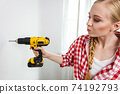 Woman using drill on wall 74192793