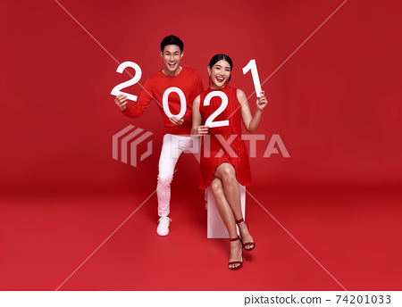 Happy asian couple in red casual attire showing number 2021 greeting happy new year with smiles 74201033