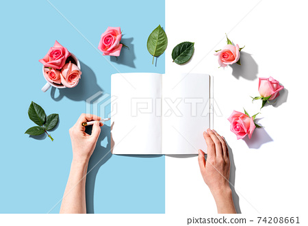 Woman writing in a notebook with pink roses 74208661